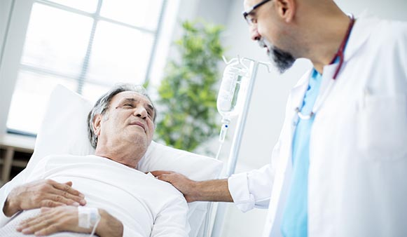 male patient in hospital talking to doctor